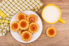 Cookies with jam in plate, milk and checkered napkin Royalty Free Stock Images