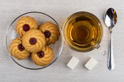 Cookies with jam in plate, cup of tea, sugar, teaspoon. Cookies with jam in transparent plate, cup of tea, sugar and teaspoon on wooden table. Top view Royalty Free Stock Photo
