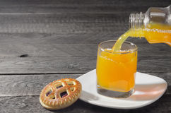 Cookies and juice is poured into a glass on gray background wood. Selective focus. Stock Image