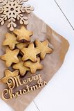 Cookies on kraft paper with wood snowflake and an inscription. Merry Christmas Royalty Free Stock Image