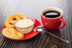 Cookies, leite condensado na bacia em pires, colher, café imagem de stock