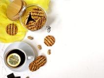 cookies lustradas com partes do chocolate e do amendoim em um frasco de vidro com uma tampa de madeira em uma tabela clara e cont Foto de Stock Royalty Free