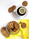 cookies lustradas com partes do chocolate e do amendoim em um frasco de vidro com uma tampa de madeira em uma tabela clara e cont Fotografia de Stock Royalty Free