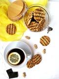 cookies lustradas com partes do chocolate e do amendoim em um frasco de vidro com uma tampa de madeira em uma tabela clara e cont Fotos de Stock