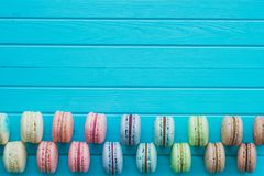 Cookies macaron or macaroons or almond cookies lie on a wooden turquoise background in checkerboard pattern top view. Copy space Stock Images