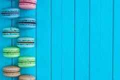 Cookies macaron or macaroons or almond cookies lie on a wooden turquoise background in checkerboard pattern, copy space.  Stock Photos