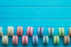 Cookies macaron or macaroons lie on a wooden turquoise background in checkerboard pattern, top view, copy space.  Stock Photo