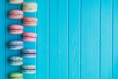 Cookies macaron or macaroons lie on a wooden turquoise background in checkerboard pattern, vintage top view, copy space.  Royalty Free Stock Photos