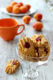 Cookies with marmalade, cup and apricots on wooden Stock Image
