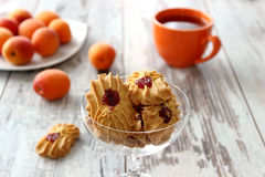 Cookies with marmalade, cup of tea and apricots on wooden Stock Photos