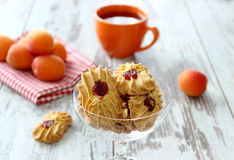 Cookies with marmalade, cup of tea and apricots on wooden Royalty Free Stock Photography