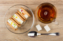 Cookies with marshmallow on saucer, cup of tea, lumpy sugar Stock Photo