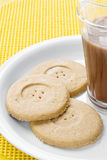 Cookies and milk. Chocolate cookies served with milk. The center of the cookie has a button hole look. Light chocolate Stock Images