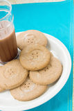 Cookies and milk. Chocolate cookies and milk. The light chocolate cookie has a button hole design Stock Images