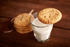 Cookies and milk. Chocolate chip cookies and a glass of milk. Vintage look. Tasty cookies and glass of milk on rustic wooden background. Food, junk-food royalty free stock images