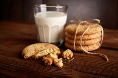 Cookies and milk. Chocolate chip cookies and a glass of milk. Vintage look. Tasty cookies and glass of milk on rustic wooden background. Food, junk-food stock images