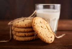 Cookies and milk. Chocolate chip cookies and a glass of milk. Vintage look. Tasty cookies and glass of milk. On rustic wooden background. Food, junk-food stock image