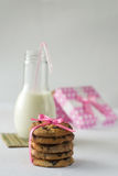 Cookies with milk and chocolate for Valentine. Biscuits with milk and piece of chocolate on the bamboo with a bow of pink ribbon box Royalty Free Stock Photo