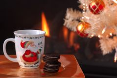 Cookies and Milk by the Fire for Santa. A cup of milk and chocolate cookies on a gold reflective plate sit in front of the fireplace and decorated Christmas Stock Photo