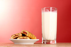 Cookies with milk on red Stock Images