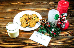 Cookies and milk for Santa Claus. Close to treat is decoration of three candles and a card with a note. Stock Photos