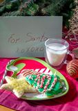 Cookies and milk for santa. A plate of cookies and milk are set out for santa under the tree Royalty Free Stock Images