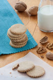 Cookies and milk. Stack of cookies with nuts on a wooden table next to a jug with milk and some nuts Royalty Free Stock Photo