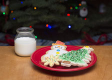 Cookies and milks for Santa. A plate of decorated sugar cookies and glass of milk for Santa Royalty Free Stock Images