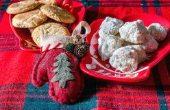 Cookies and mitten for Christmas. Cinnamon sugar cookies and Mexican wedding cookies  with a cute  mitten  ornament for Christmas Royalty Free Stock Image