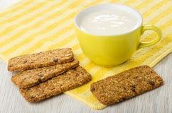 Cookies-muesli with chocolate, cup with yogurt on napkin on wooden table. Few of cookies-muesli with chocolate, yellow cup with yogurt on striped napkin on light stock image