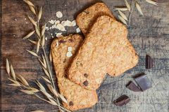 Cookies muesli made with raw organic cereals rice flour with chocolate on old wooden cutting Board. Stock Image