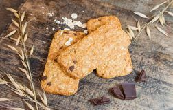 Cookies muesli made with raw organic cereals rice flour with chocolate on old wooden cutting Board. Royalty Free Stock Photography