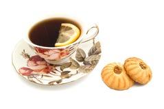 Cookies and mug of tea with lemon Stock Photos