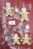 Cookies na obscuridade - tabela de madeira vermelha dos homens de pão-de-espécie do Natal Imagens de Stock