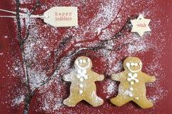 Cookies na obscuridade - tabela de madeira vermelha dos homens de pão-de-espécie do Natal Imagem de Stock