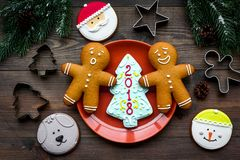 Cookies for New Year. Gingerbread man and spruce with lettering 2018 near spruce branch on wooden background top view.  Stock Photography