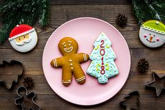 Cookies for New Year. Gingerbread man and spruce with lettering 2018 near spruce branch on wooden background top view.  Stock Photo