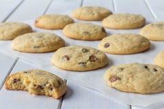 Cookies no papel do cozimento com um comido em parte foto de stock royalty free