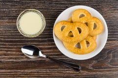 Cookies nos pires, leite condensado na bacia, colher na tabela imagem de stock