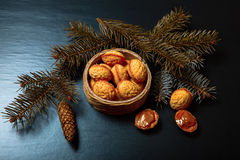Cookies Nuts with sweet filling in a wicker basket with Christmas tree branches on a black background. New Year's Royalty Free Stock Photos