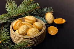 Cookies Nuts with sweet filling in a wicker basket with Christmas tree branches on a black background. New Year's Royalty Free Stock Photo