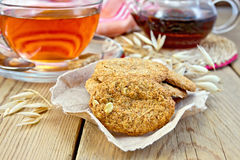 Cookies oatmeal with spikelet and napkin on board Stock Photos