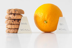 Cookies or orange fruit, diet choice concept, calorie count Royalty Free Stock Image