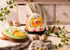 Cookies with painted easter bunny and chicken near decorative buffet and green napkin on white cutting boards stock image