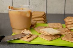 Peanut butter on cookies. Cookies with peanut butter on bright green board royalty free stock photo