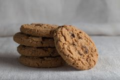 Cookies pile with chocolate chip on light textile background. Delicious morning snacks for breakfast, brunch and lunch. Appetizing, healthy, sweet, scrummy Royalty Free Stock Photography
