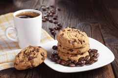 Cookies in plate and coffee cup. Cookies with chocolate in plate and cup of hot coffee on dark wooden table Royalty Free Stock Image