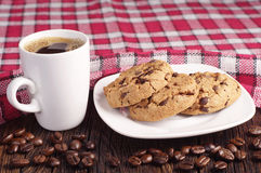 Cookies in plate and coffee cup. Chocolate cookies in plate and cup of hot coffee on wooden table covert tablecloth Stock Image