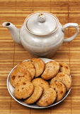 Cookies on a plate and a teapot. Cookies with chocolate on a plate and a teapot Royalty Free Stock Photography