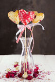 Cookies pops in the form of heart and heart from fabric in a pat. Tern a red cage with buds of roses Royalty Free Stock Images